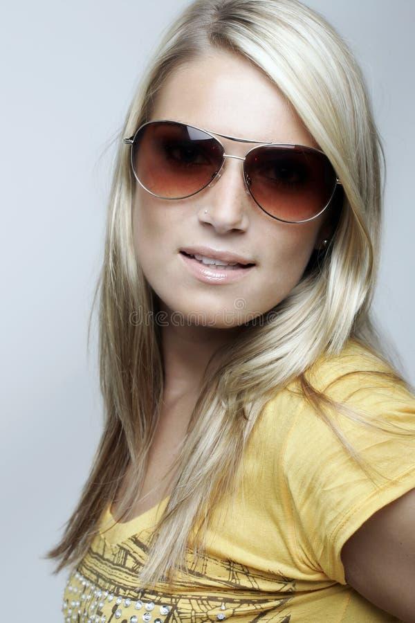 Skönhetstående av en blond kvinna med solglasögon arkivbild