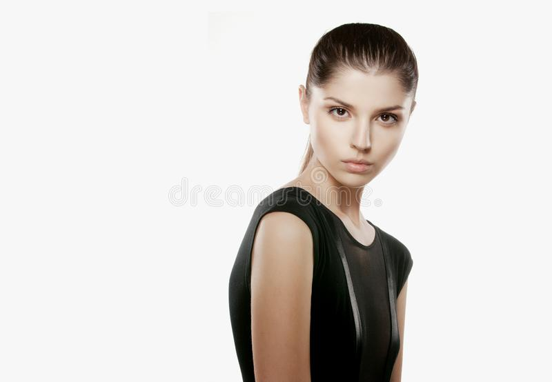 Skönhetstående av en brunettmodell i elegant svart klänning, med åtsittande hår som poserar innegrej, över vit bakgrund royaltyfri bild