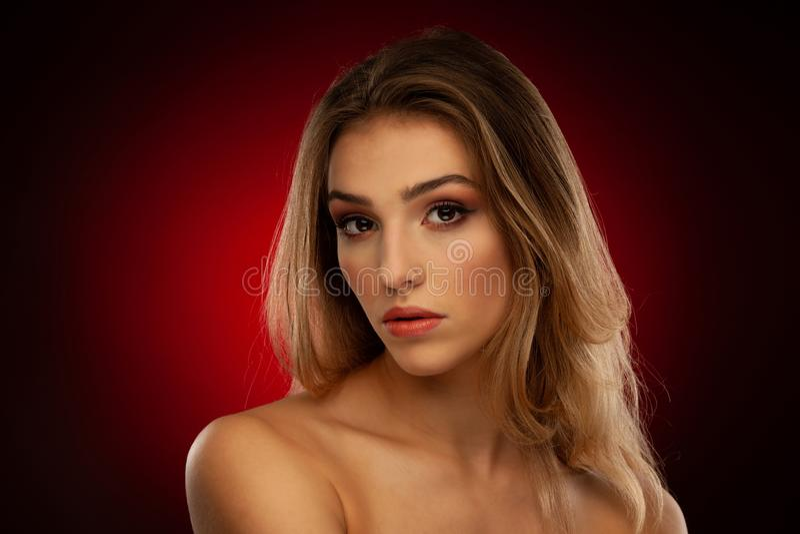 Skönhetstående av en härlig ung kvinna med brunt långt hår över mörkt - röd bakgrund royaltyfri fotografi