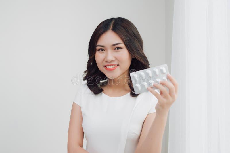 Skönhetstående av en härlig ung kvinna med preventivpillerar royaltyfri foto