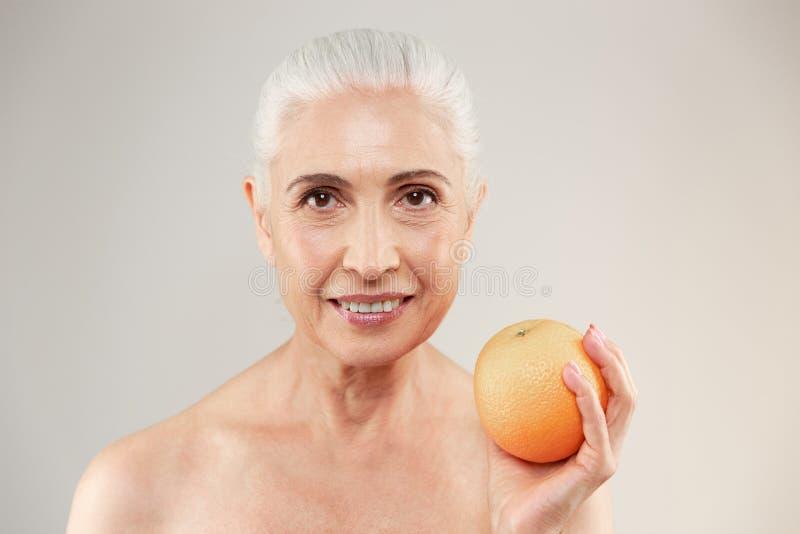 Skönhetstående av en le halv naken äldre kvinna fotografering för bildbyråer