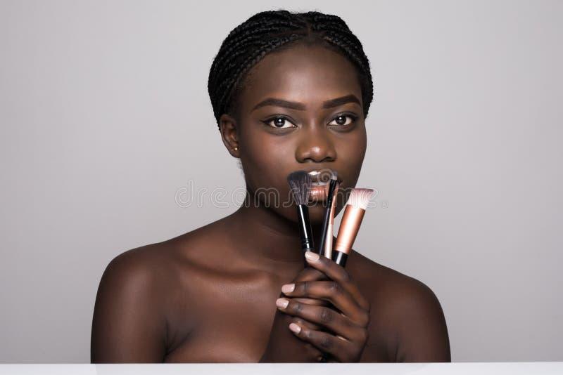 Skönhetstående av en le naken afrikansk kvinna för härlig halva som poserar med sminkborstar över vit bakgrund arkivbilder
