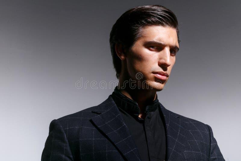 Skönhetstående av en manlig modell i den svarta dräkten, frisyr som ser rynka pannan, på en vit bakgrund royaltyfria bilder