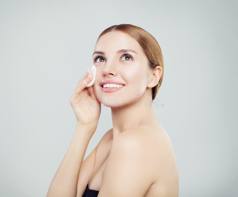 Skönhetstående av en ung attraktiv kvinna som gör ren hennes framsida arkivbild