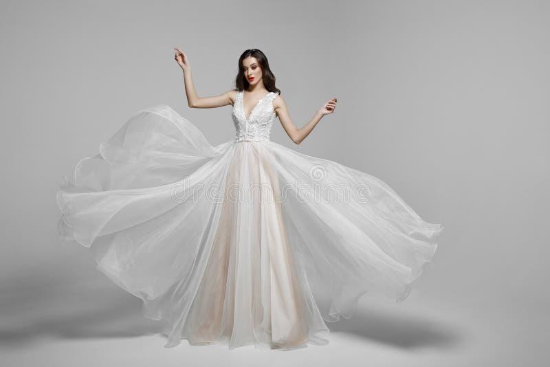 Skönhetstående av en ung kvinna i att gifta sig den långa klänningen för mode i vinkande flygatyg, torkduk som fladdrar i vind royaltyfri foto