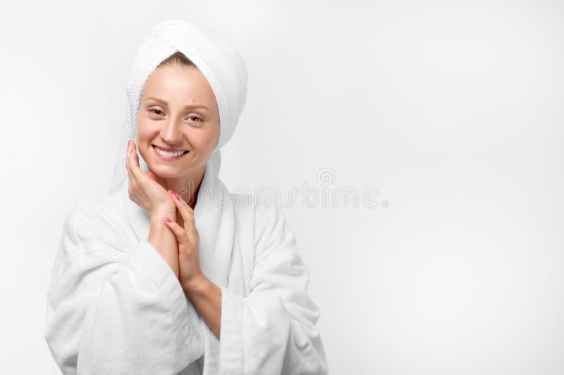 Skönhetstående av kvinnan som bär en handduk och en vitbadrock royaltyfria foton