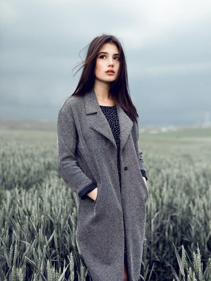 Skönhetstående en brunettflicka i en grå överrock, ställning i grönt fält, på en mörk himmelbakgrund royaltyfria foton