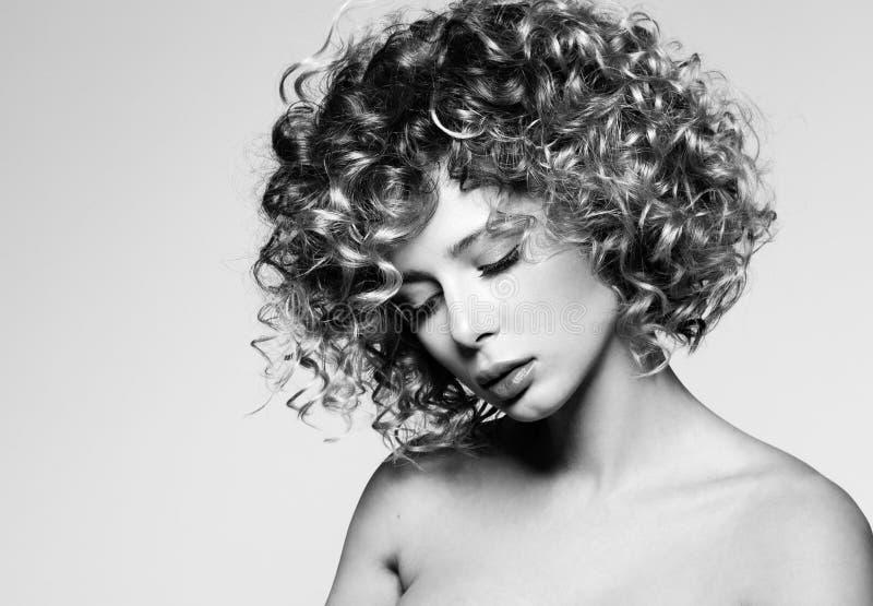 Skönhetståenden av den unga kvinnan med ögon stängde sig Härlig frisyr med lockigt hår arkivbilder