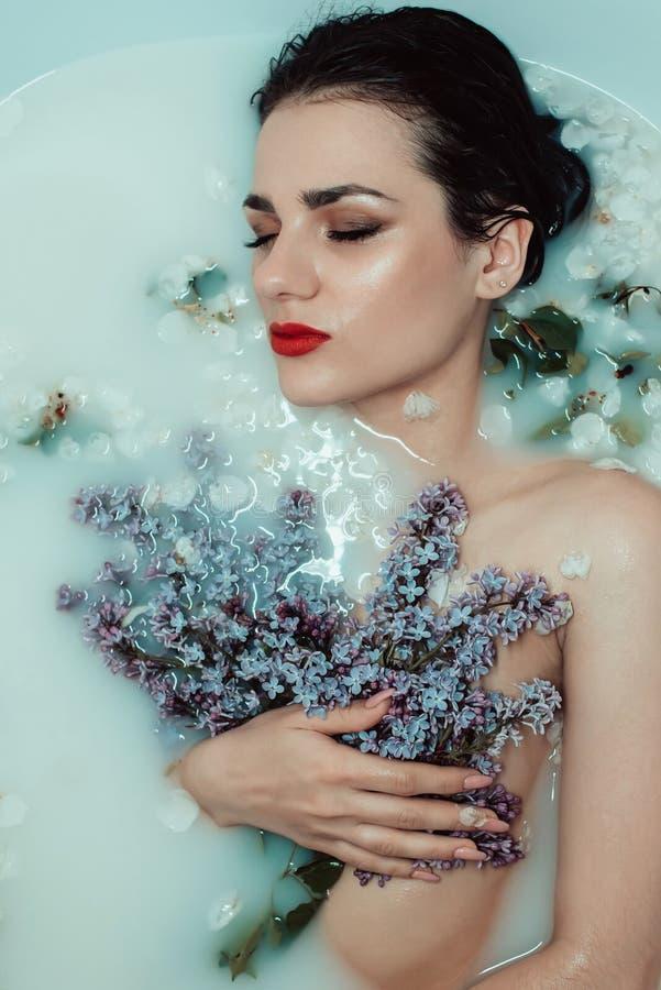 Skönhetståenden av en härlig ung flicka i ett bad med mjölkar och blommor av lilan royaltyfri foto