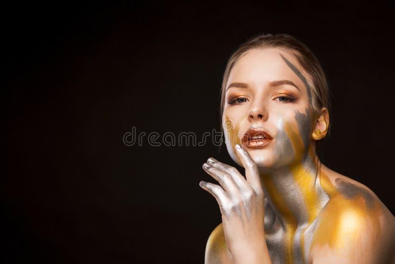 Skönhetstudiostående av den lyxiga blonda flickan med guld och si arkivfoto