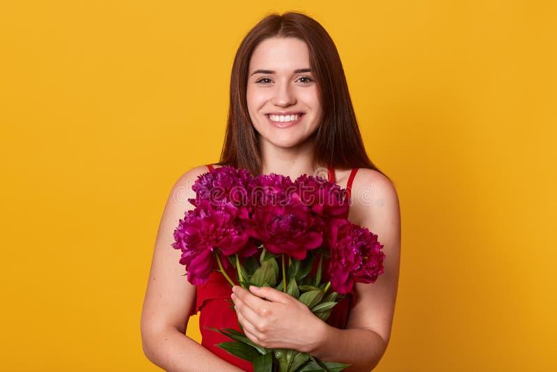 Skönhetstudiostående av den romantiska modellkvinnan med burgundy pionblommor Attraktivt kvinnligt posera med det toothy leendet  arkivfoto