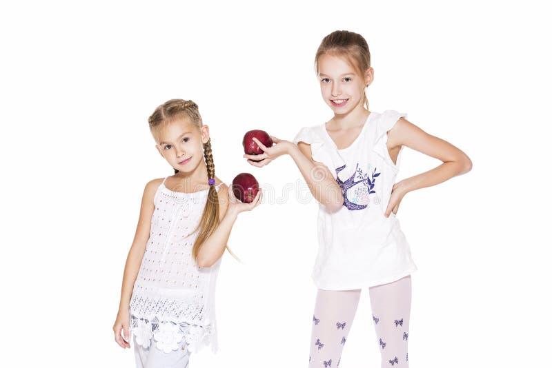 Skönhetunga flickor med nya äpplen arkivbilder