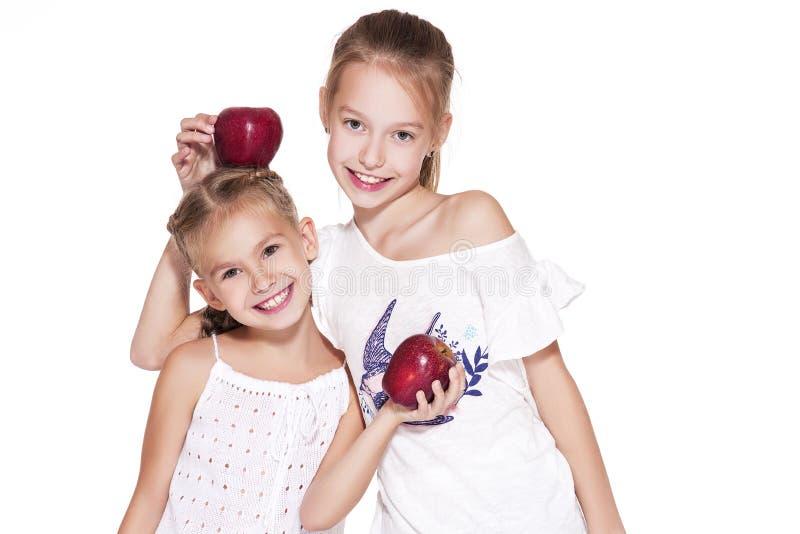 Skönhetunga flickor med nya äpplen fotografering för bildbyråer