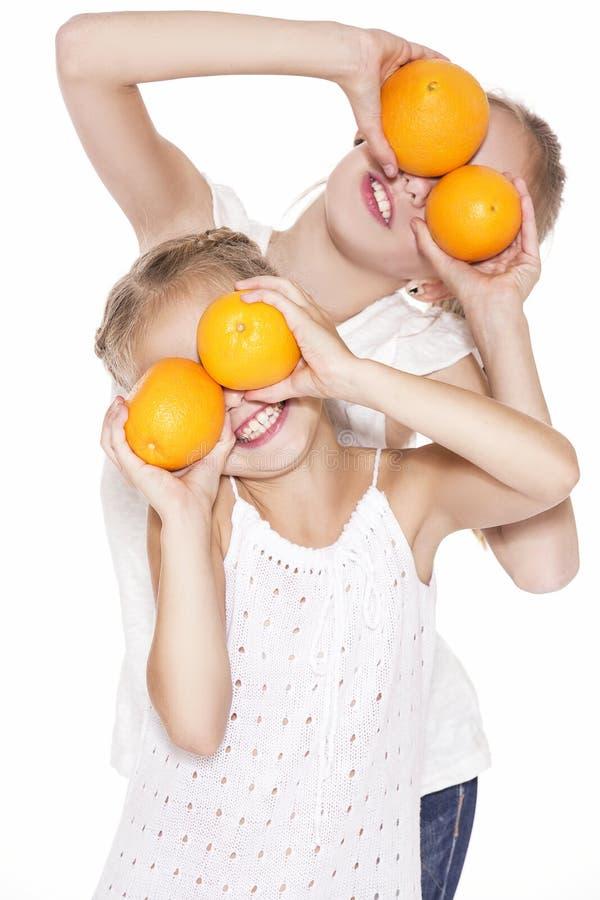 Skönhetunga flickor med nya apelsiner fotografering för bildbyråer