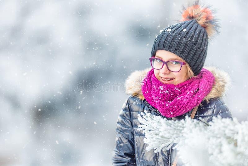 Skönhetvinterflickan som blåser insnöad frostig vinter, parkerar eller utomhus Flicka och kallt väder för vinter arkivbild