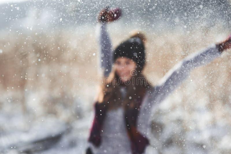 Skönhetvinterflickan som blåser insnöad frostig vinter, parkerar utomhus Flygsnöflingor solig dag Backlit Joyful skönhet royaltyfria bilder