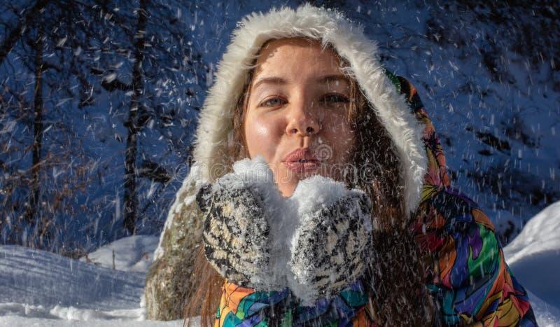 Skönhetvinterflickan som blåser insnöad frostig vinter, parkerar utomhus Flygsnöflingor solig dag Backlit Joyful skönhet arkivbild