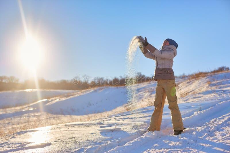 Skönhetvinterflickan som blåser insnöad frostig vinter, parkerar utomhus Flygsnöflingor solig dag Backlit Ung kvinna för skönhet  royaltyfri bild