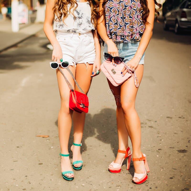 Skörd av stilfulla flickor som rymmer den rosa och röda handväskan royaltyfri foto