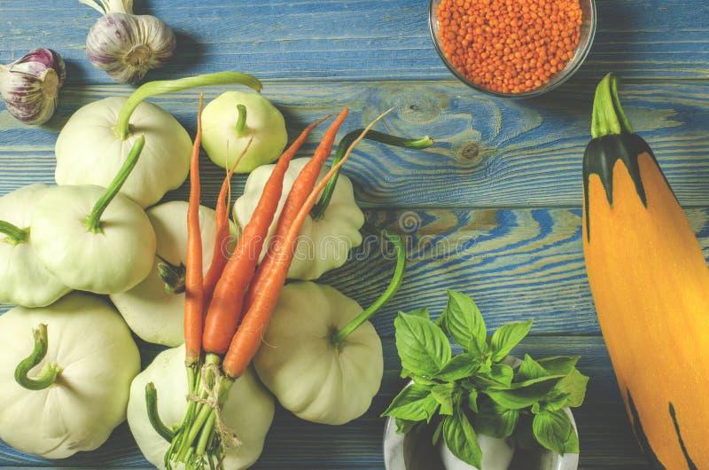 Skörd Patisons, vitlök, morötter, basilika, linser och zucchinilögn på en blå trätabell arkivbilder