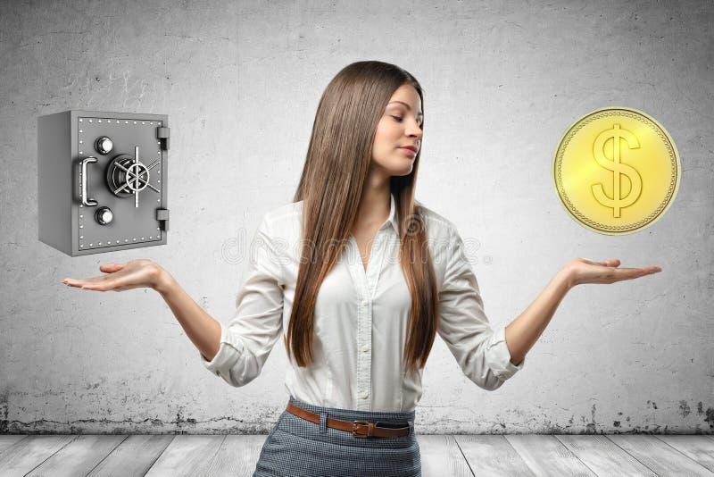 Skördbild av den unga attraktiva affärskvinnan, händer på sidor och att få att sväva det låsta pengarvalvet och det enorma guld-  arkivfoton