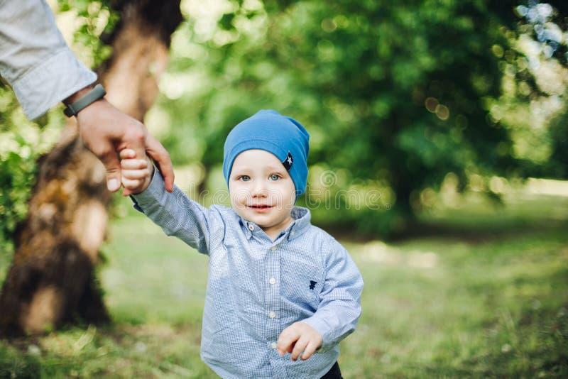 Skörden av fadern som rymmer vid handen, behandla som ett barn pojken som går i sommar, parkerar arkivfoton