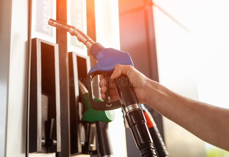 Skördhand som tar bränsleutmataren från pumpen arkivbild