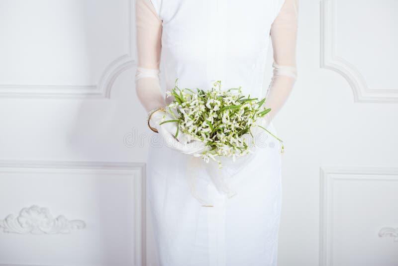 Skördkvinna i den eleganta klänningen som rymmer blommor arkivbild