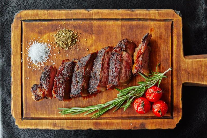 Skört, kokt, skuret i skivor, liggande på träskivor, dekorerat med tomater, aragon, örter royaltyfria foton