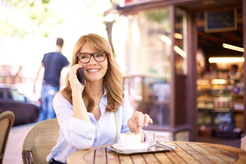 Sköt av den mellersta åldriga kvinnan som sitter i coffee shop och gör en appell arkivbilder