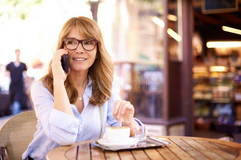 Sköt av den mellersta åldriga kvinnan som sitter i coffee shop och gör en appell arkivfoto