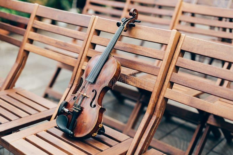 Sköt av fiolen på trästol, med inga personer Klassiskt musik och konstbegrepp symfoni Horisontalutomhus- skott royaltyfri foto