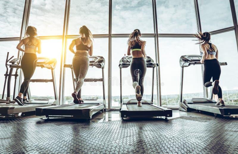 Sköt av fyra kvinnor som joggar på trampkvarnen på den vård- klubban arkivfoton