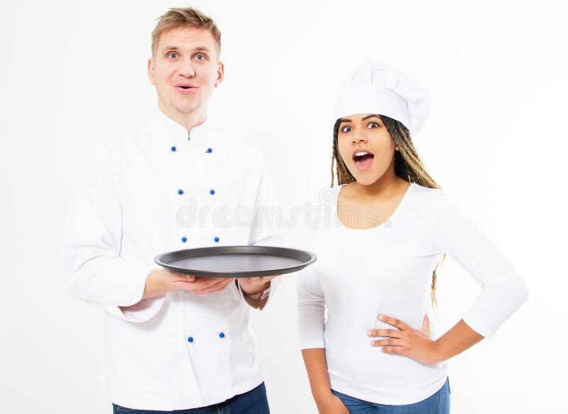 Sköt av två emotionella gladlynta yrkesmässiga kökkockar som tillsammans poserar det tomma magasinet för hållen på den vita bakgr royaltyfri fotografi