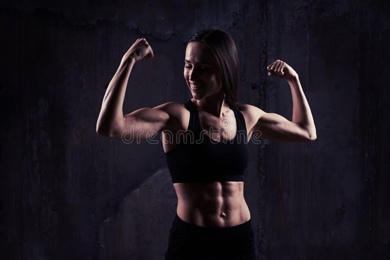 Sköt inomhus av den unga säkra muskulösa kvinnan som visar relien royaltyfri foto