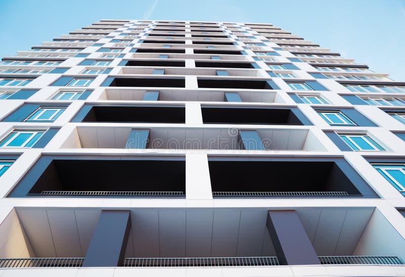 Sköt underifrån av modern och ny hyreshus Foto av ett högväxt flerbostadshus med balkonger mot en blå himmel royaltyfria bilder