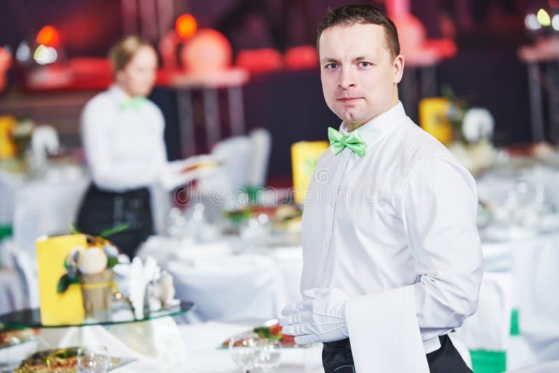 Sköta om service uppassare som är tjänstgörande i restaurang royaltyfri bild