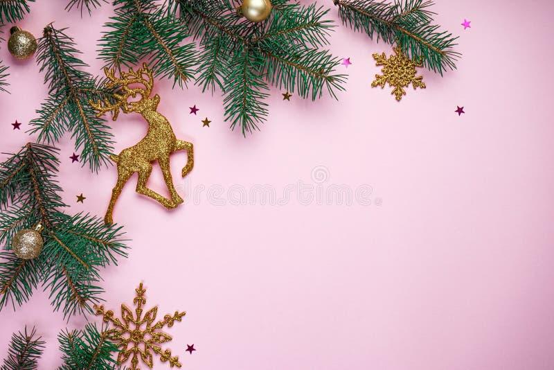 Skład świąteczny Gałęzie choinkowe, z noworocznymi złotymi ozdobami i wielokolorowymi słodyczami na różowym tle zdjęcia stock