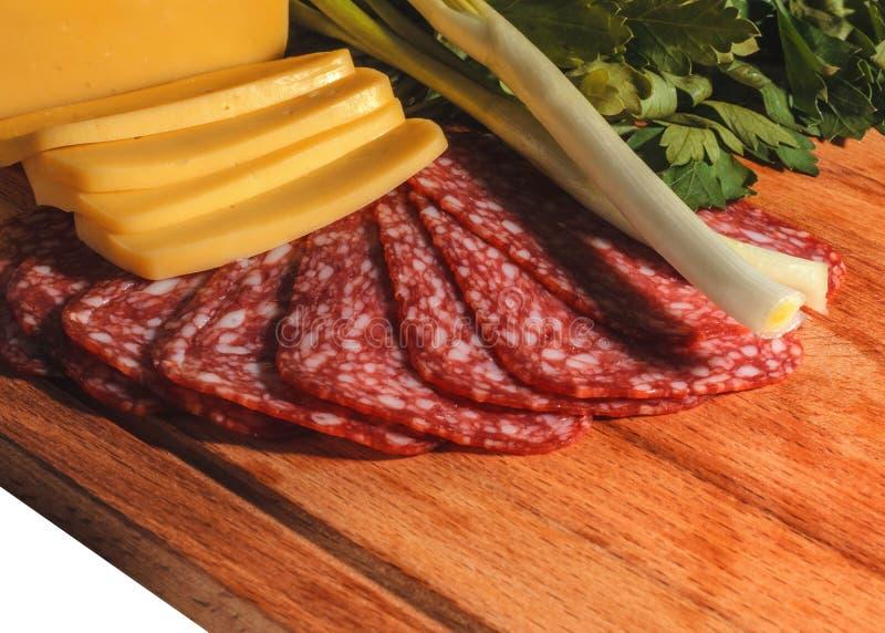 Skład apetyczna kiełbasa, ser, zielenie i cebule na drewnianej desce, odizolowywa fotografia stock