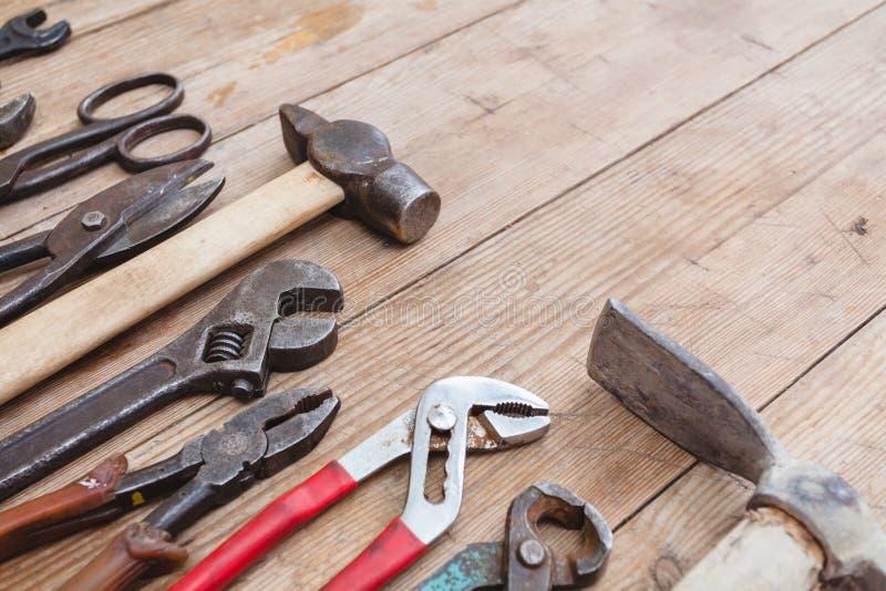 Skład budów narzędzia na starej powyginanej drewnianej powierzchni narzędzia: cążki, fajczany wyrwanie, śrubokręt, młot, metalu m obrazy royalty free