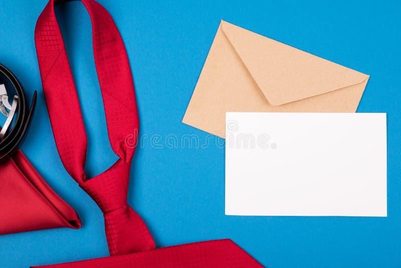 Skład czerwony szyja krawat, kieszeń kwadrat, pasek, rzemiosło koperta i pusta karta na błękitnym cyan tle, zdjęcie royalty free