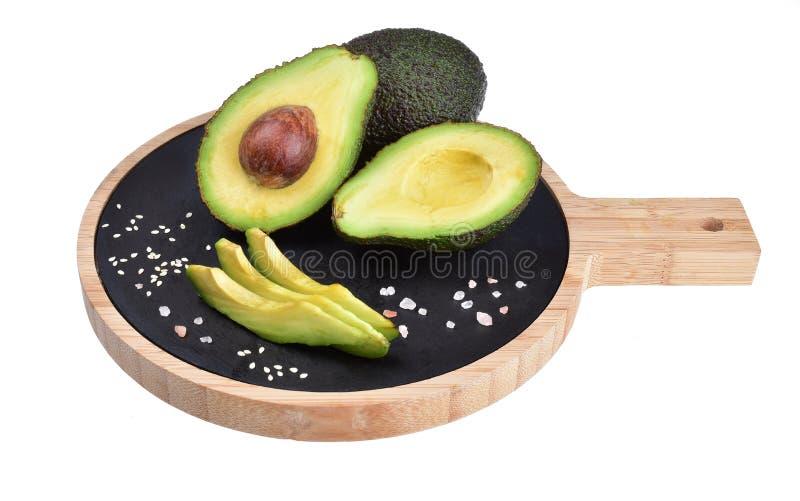 Skład dojrzali świezi avocados, pikantność i drewniana tnąca deska, zdjęcie royalty free
