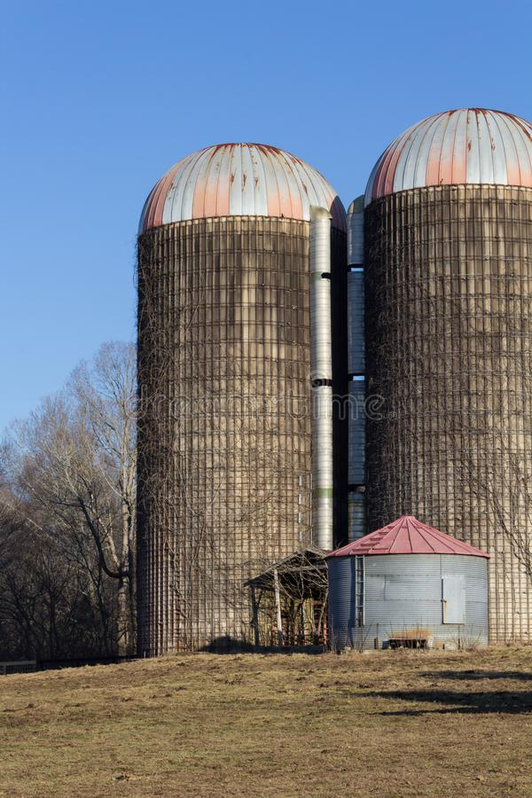 Skład dwa wielki i mali jeden silosu w zima krajobrazie obraz stock