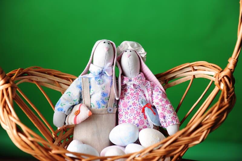 skład Easter Miękkie zabawki króliki handmade z jajkami w łozinowym koszu Szczegół wystrój Zielony tło zdjęcie stock