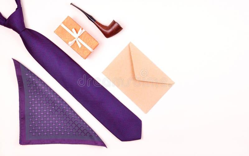 Skład fiołkowy szyja krawat, prezenta pudełko w, kieszeń kwadrat, rzemiosło papierowa koperta i dymić tabaczną drymbę na tle, zdjęcia stock