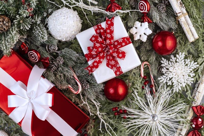 Skład liści świątecznych z czerwonymi i białymi darami z wstążką, kulami, płatkami śniegu, jagodami, śnieżnymi gałęziami, widok z zdjęcie stock