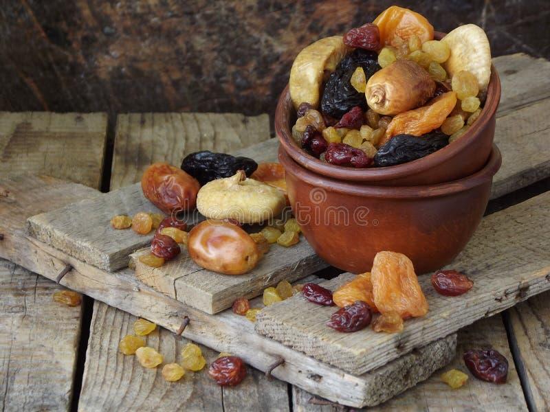 Skład od różnych rozmaitość wysuszone owoc na drewnianym tle - daty, figi, morele, przycinają, rodzynki, cranberrie fotografia stock