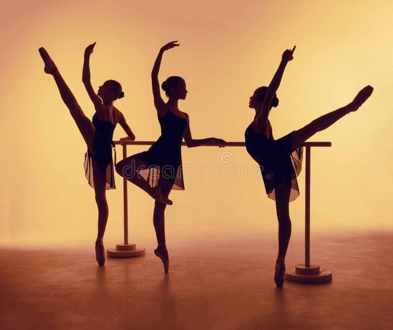Skład od sylwetek trzy młodego tancerza w balet pozach na pomarańczowym tle zdjęcie stock