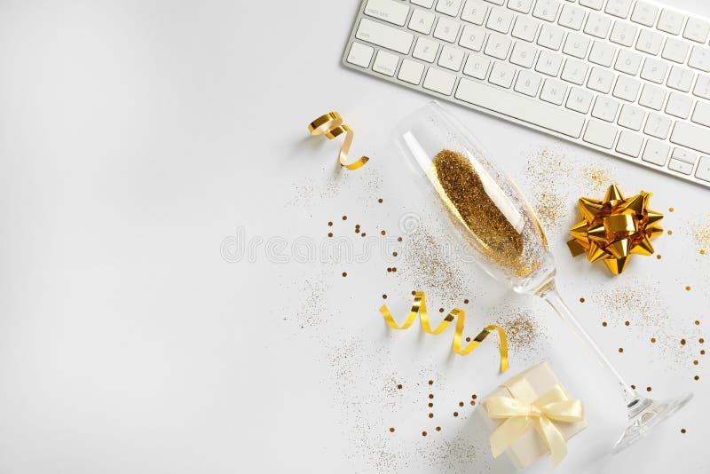 Skład szampański szkło z złocistym błyskotliwości, klawiatury i prezenta pudełkiem na białym tle, Komicznie świętowanie obrazy royalty free