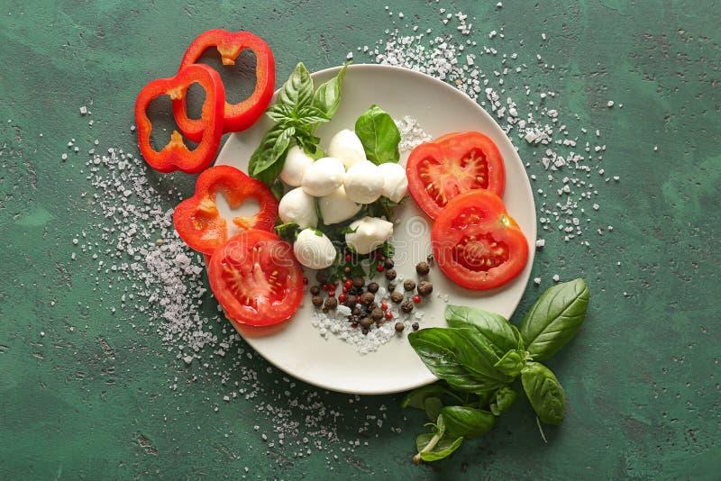 Skład z świeżym basilem, warzywami i mozzarella serem na kolorze, textured tło fotografia royalty free